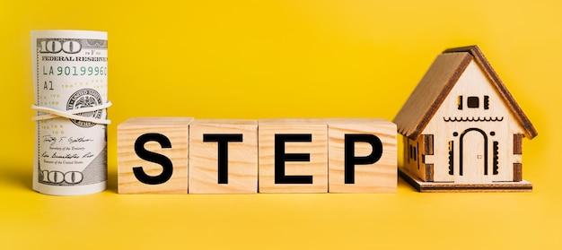 Step con modello in miniatura di casa e denaro su uno spazio giallo