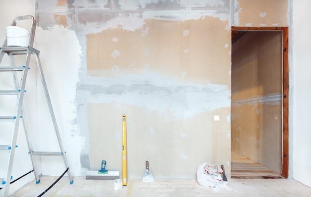 Una scala a pioli con strumenti di pittura in una stanza di una casa o di un appartamento. preparazione per stucco sul muro o pittura. concetto di riparazione o ristrutturazione della casa.