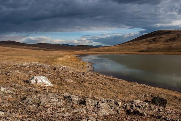 Lago delle steppe con pietre in primo piano e colline in lontananza, nuvole nel cielo