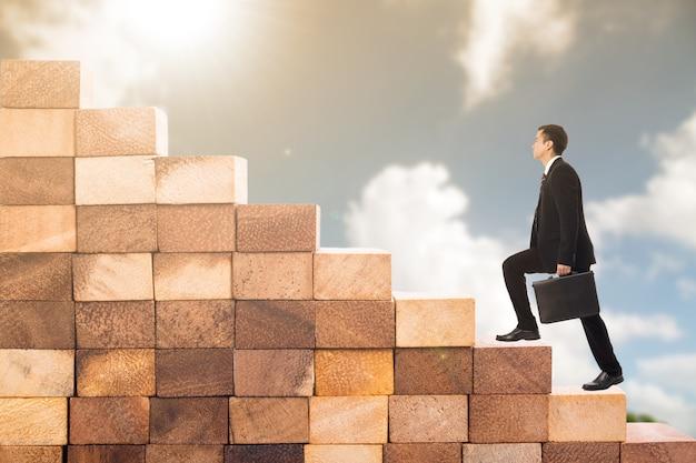 Passi verso il successo, l'uomo d'affari inizia a salire le scale di legno per andare avanti con la sua attività di successo.