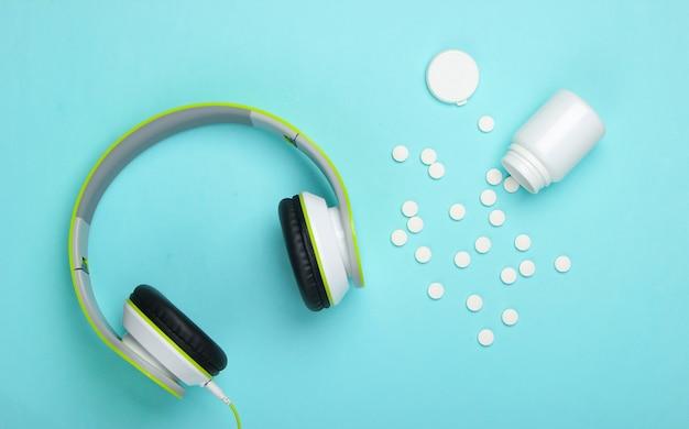 Cuffie stereo e pillole su una superficie blu