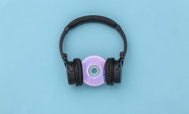 Cuffie stereo con disco cd su sfondo blu. vista dall'alto