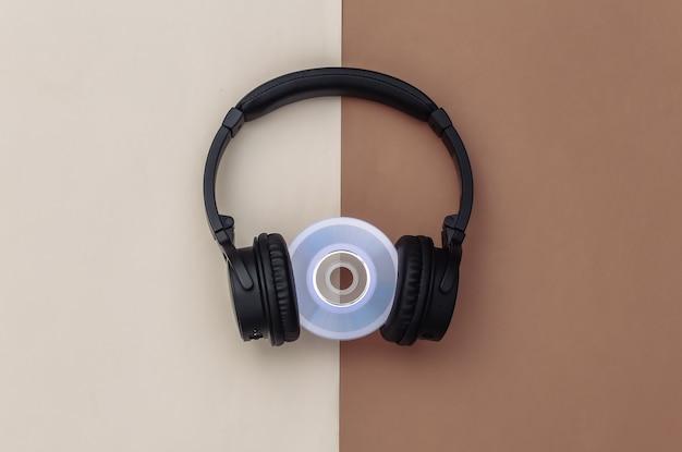 Cuffie stereo con disco cd su sfondo beige marrone. vista dall'alto