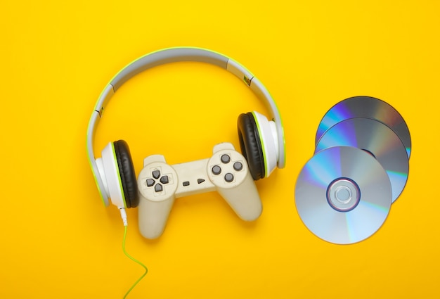 Cuffie stereo con gamepad, dischi cd su superficie gialla