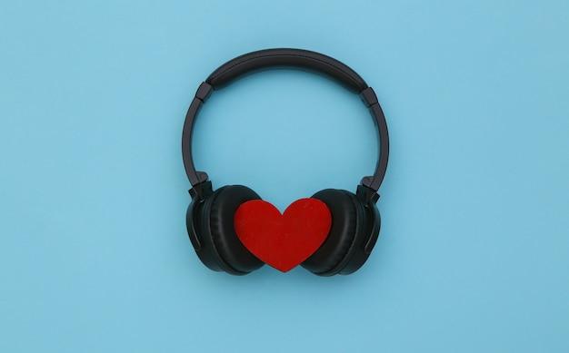 Cuffie stereo con cuore su sfondo blu. amante della musica