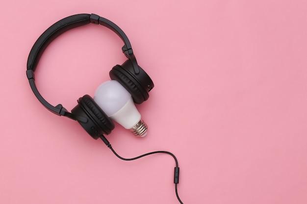 Cuffie stereo con lampadina su sfondo rosa. vista dall'alto