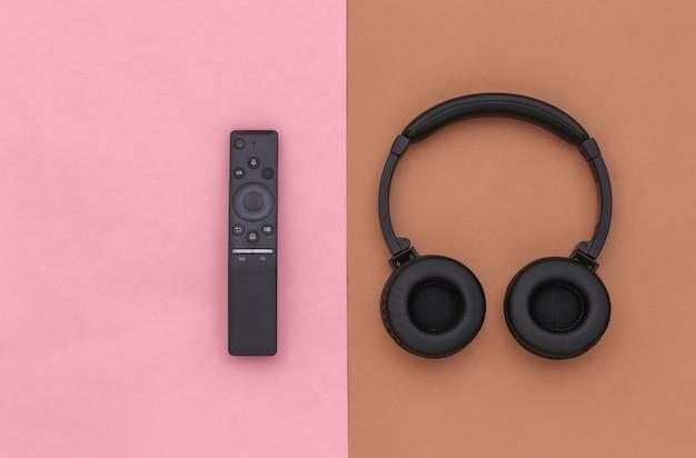 Cuffie wireless stereo e telecomando della tv su uno sfondo rosa-marrone. vista dall'alto