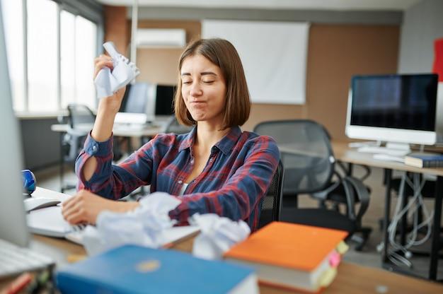 Lo specialista it femminile stessed lavora al computer in ufficio. programmatore web o designer sul posto di lavoro, occupazione creativa. moderna tecnologia dell'informazione, team aziendale