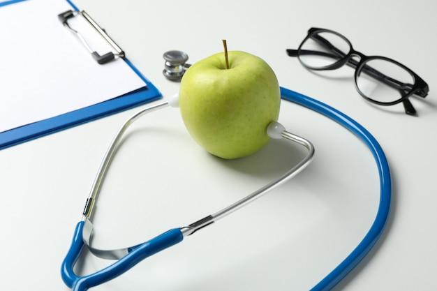 Stetoscopio e mela su superficie bianca, fine in su