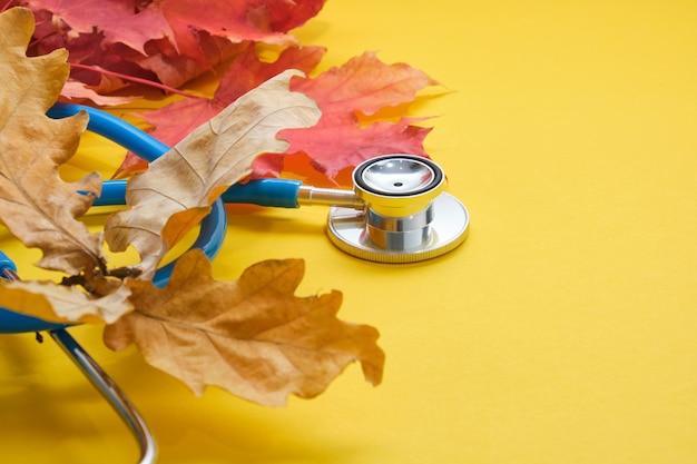Stetoscopio e foglie d'acero autunnali su sfondo giallo