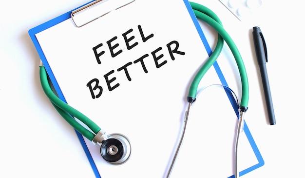 Stetoscopio e appunti blu con testo sentire meglio sul foglio di lavoro