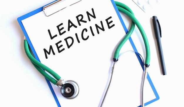 Stetoscopio e blocco appunti blu con learn medicine