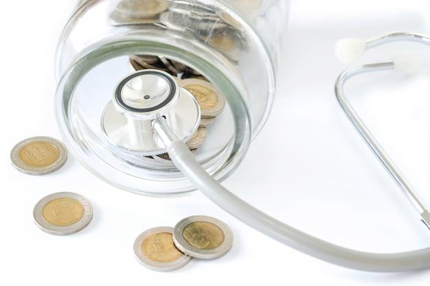Stetoscopio sulla bottiglia e moneta su fondo bianco. concetto di controllo sanitario finanziario o costo delle imprese, analisi finanziaria, audit o contabilità.