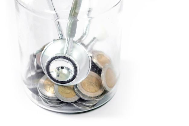 Stetoscopio, bottiglia e moneta su sfondo bianco. concetto per il controllo dello stato di salute delle finanze o il costo del business, analisi finanziaria, audit o contabilità.