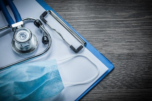 Maschera facciale medica usa e getta degli appunti dello stetoscopio sulla tavola di legno dell'annata