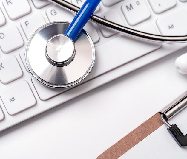 Stetoscopio sulla tastiera del computer. il medico scrive il concetto di trattamento di cura a lungo termine caso medico close up spazio copia macro