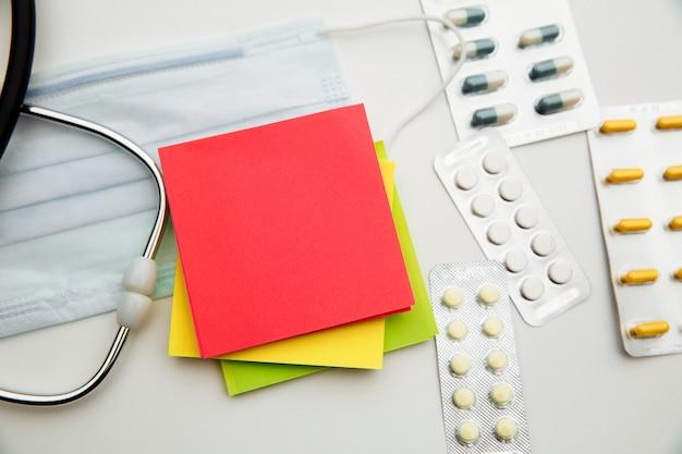 Stetoscopio, droghe, maschera per il viso e foglietti adesivi colorati per il testo su bianco.