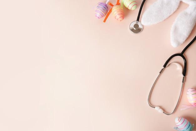 Stetoscopio e uova di pasqua, orecchie da coniglio su sfondo rosa con uno spazio di copia