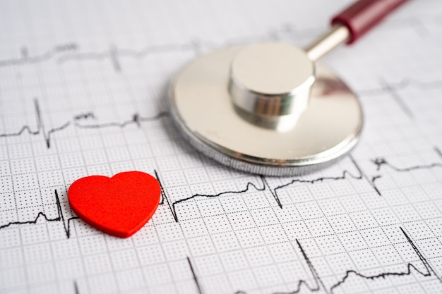 Stetoscopio sull'elettrocardiogramma (ecg) con cuore rosso, onda cardiaca, attacco di cuore, rapporto del cardiogramma.