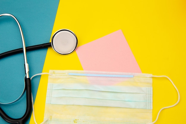 Stetoscopio, maschera facciale e nota adesiva rosa per testo colorato.
