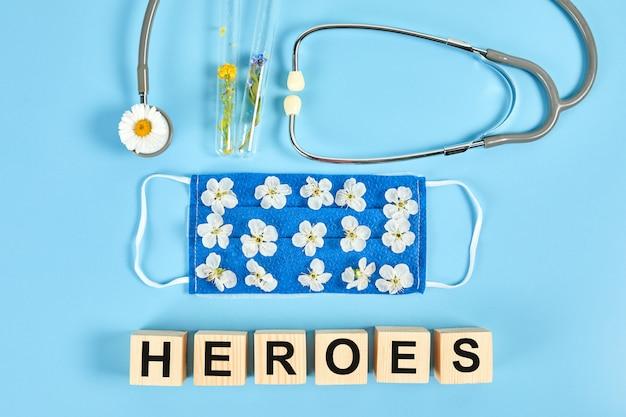 Stetoscopio, fiori e mascherina protettiva medica con cubi di legno. testo eroi, gratitudine per il personale medico e i medici