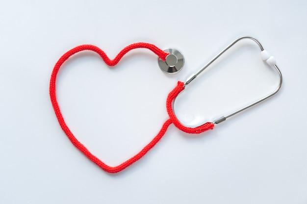 Stetoscopio formando il cuore con il suo cavo su sfondo bianco. concetto di assistenza sanitaria. cuore rosso fatto di filato per maglieria. spazio per il testo. focalizzazione morbida. vista dall'alto. lay piatto.