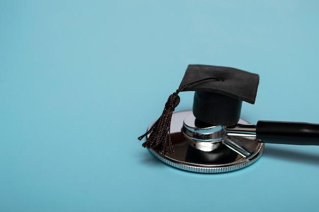 Stetoscopio e cappello da laureato, su sfondo blu, vista dall'alto, conseguimento di laurea in background medico, sfondo