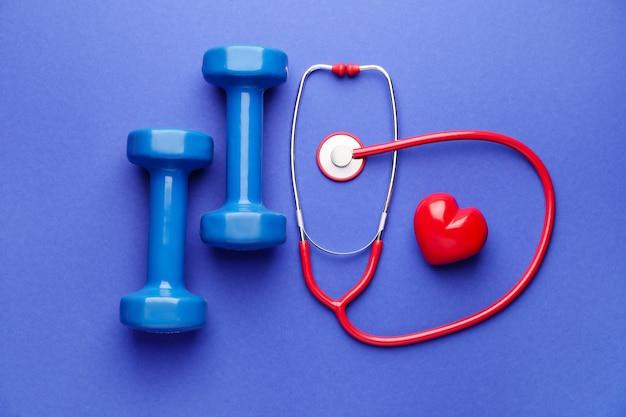 Stetoscopio, cuore e manubri su sfondo colorato