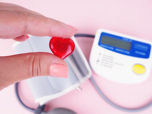 Stetoscopio, a forma di cuore, monitor della pressione sanguigna. mano femminile che tiene il cuore, la pressione sanguigna.
