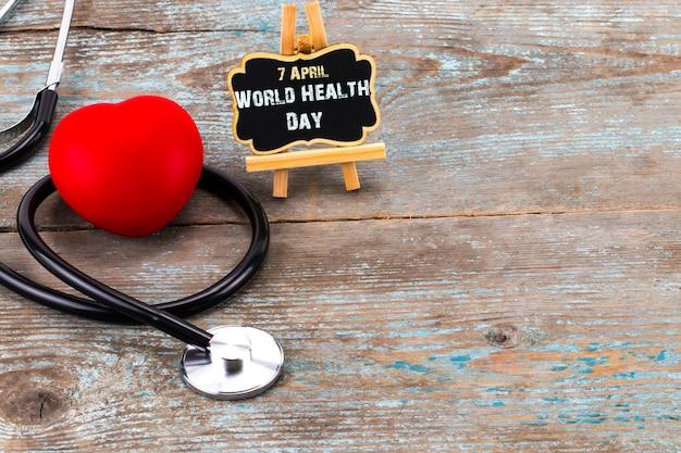Stetoscopio e simbolo del cuore con iscrizione giornata mondiale della salute su fondo di legno con spazio di copia.