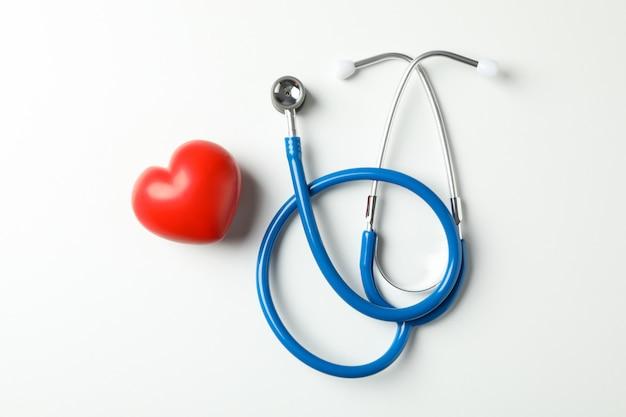 Stetoscopio e cuore su sfondo bianco, spazio per il testo