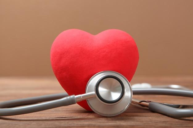 Stetoscopio e cuore su fondo in legno salute medicina