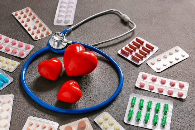 Stetoscopio, cuori e pillole su sfondo grigio. concetto di cardiologia