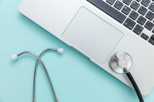 Computer portatile della tastiera dello stetoscopio isolato su priorità bassa blu. la moderna tecnologia dell'informazione medica e il software avanzano il concetto. diagnostica e riparazione di computer e gadget. vista dall'alto piatta