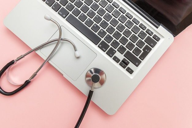Computer portatile della tastiera dello stetoscopio isolato su fondo rosa. la moderna tecnologia dell'informazione medica e il software avanzano il concetto. diagnostica e riparazione computer e gadget. vista dall'alto piatta