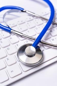 Stetoscopio sulla tastiera sul fondo bianco della tavola.