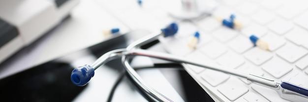 Lo stetoscopio si trova sulla tastiera bianca del computer. concetto di cure e servizi medici