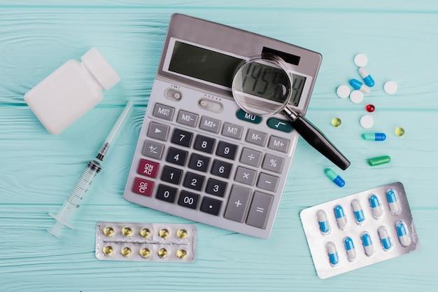 Stetoscopio e lente d'ingrandimento su un simbolo di calcolatrice per costi sanitari o assicurazione medica. spese sanitarie.
