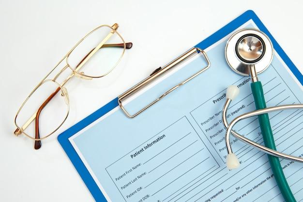 Stetoscopio e modulo di appuntamento del paziente su un tavolo bianco