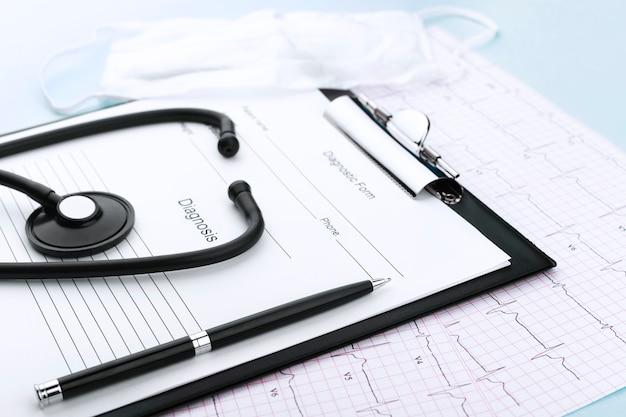 Stetoscopio, penna, appunti su cardiogramma con maschera su sfondo blu