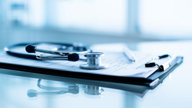 Stetoscopio e penna che pongono sullo spazio in bianco delle informazioni del paziente.