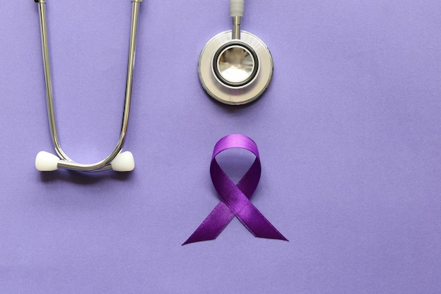 Stetoscopio e persona con nastro viola su viola, simbolo di consapevolezza di alzheimer, sanità e medicina.