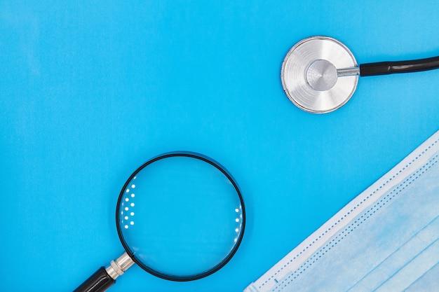 Stetoscopio o phonendoscope, lente d'ingrandimento e maschera medica sui precedenti blu con lo spazio della copia. concetto di protezione dal coronavirus. avvicinamento