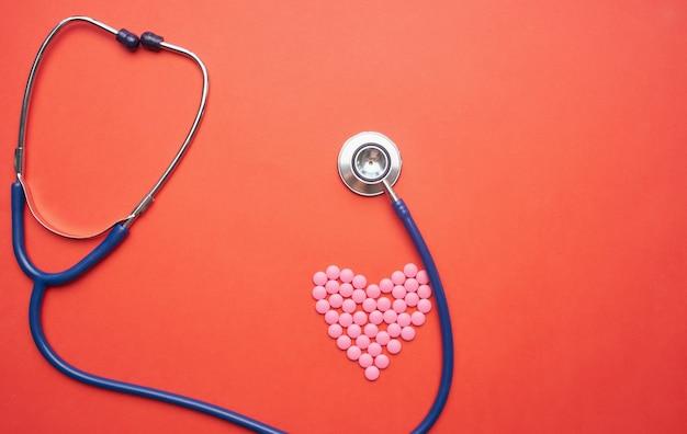 Stetoscopio e pillole a forma di cuore su una parete rossa medicina salute vitamine.