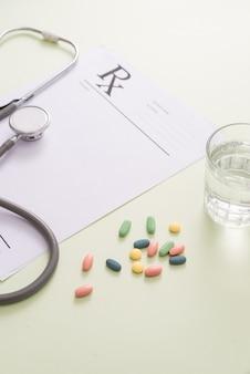 Stetoscopio, pillole e bicchiere d'acqua su sfondo verde chiaro. concetto di medicina