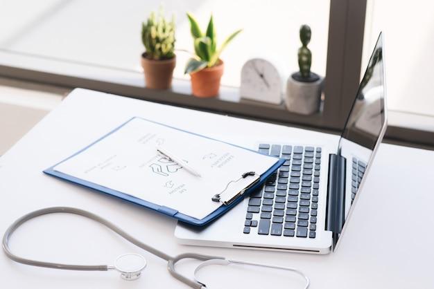 Stetoscopio, pillole, laptop su superficie bianca. concetto di medicina
