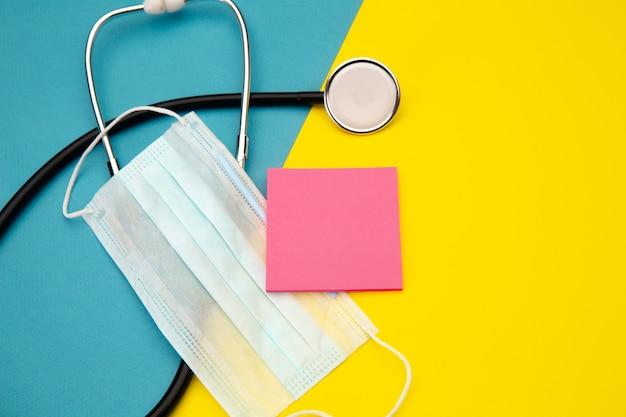 Stetoscopio e nota adesiva rosa per il testo sopra la maschera per il viso su colorato