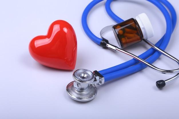 Stetoscopio, cuore rosso e pillole assortite sul tavolo bianco con spazio per il testo.