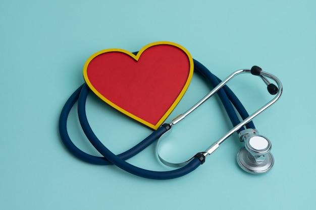 Uno stetoscopio e un cuore rosso su sfondo blu. il concetto di cardiologia.