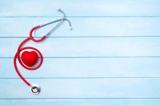 Stetoscopio e cuore rosso su legno blu